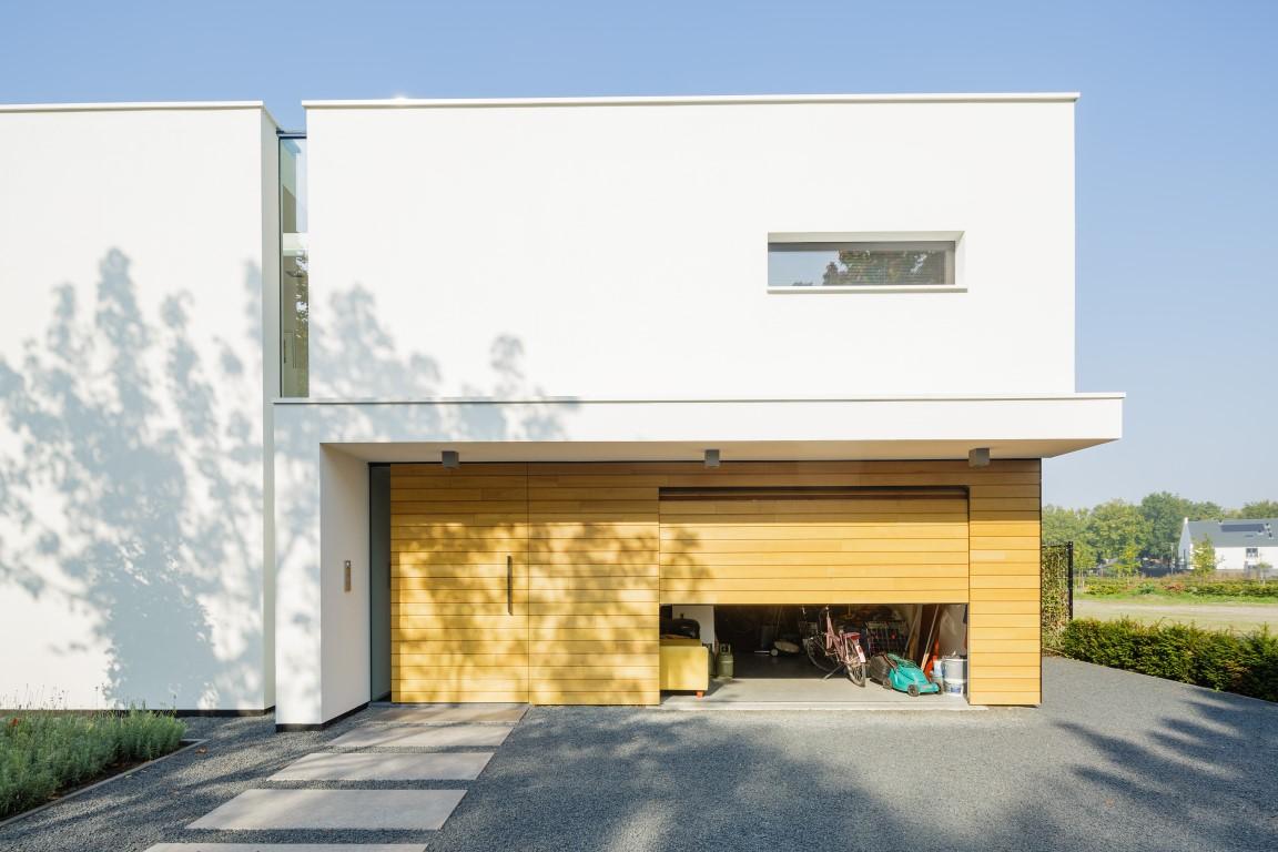 Elektrisch houten sectionaaldeur en voordeur omringt met gevelbekleding
