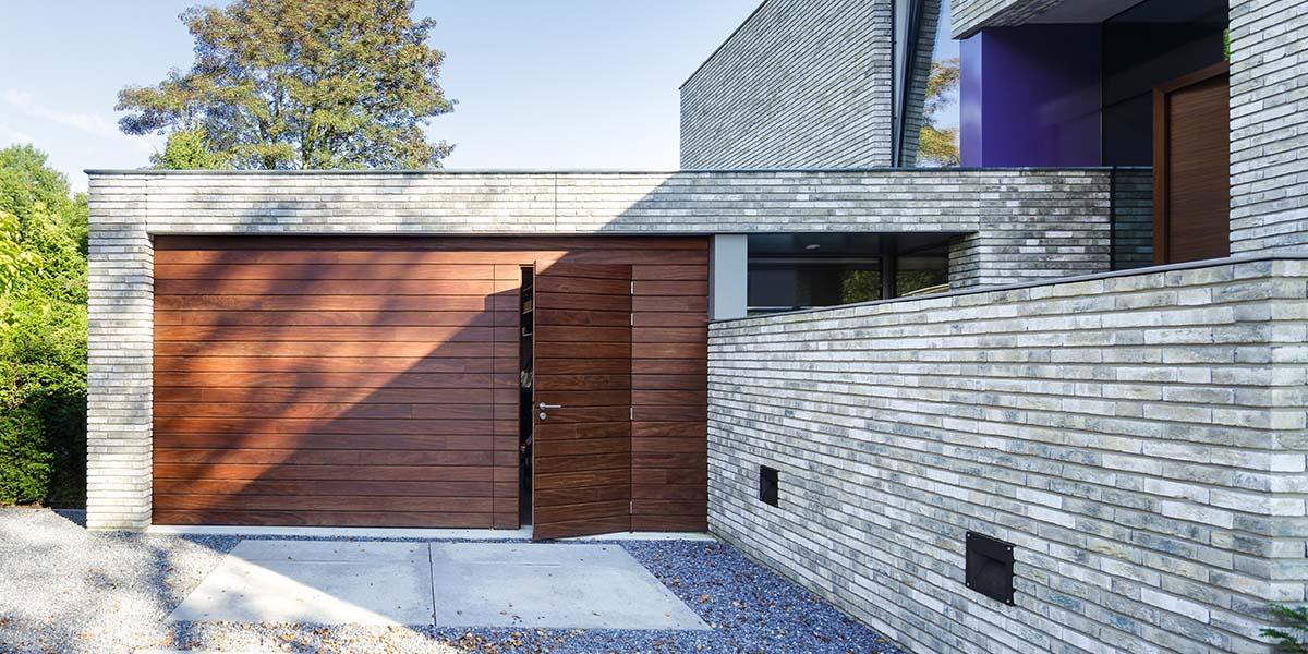 https://garagedeuren.s3.amazonaws.com/20180808094649/houten-garage-deur-afrormosia-gevelbeklding-voordeur-4.jpg
