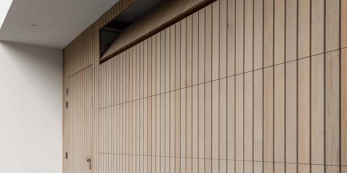 verticale-garagedeur-en-loopdeur-in-1-vlak-met-de-wand-Red-Cedar-latten-1