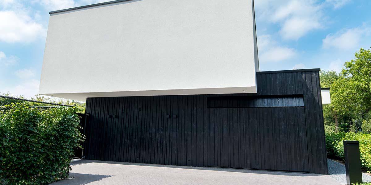 Zwarte-houten-garagedeur-verticaal-geprofileerd-in-drie-breedtes-gelijk-met-gevel-24