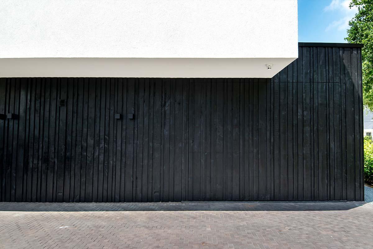 Zwarte-houten-garagedeur-verticaal-geprofileerd-in-drie-breedtes-gelijk-met-gevel