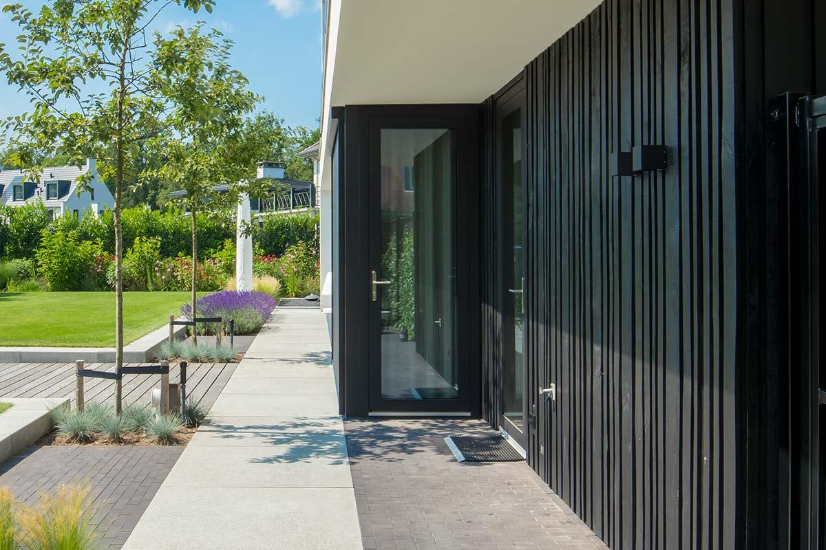 Zwarte-houten-garagedeur-verticaal-geprofileerd-in-drie-breedtes-gelijk-met-gevel-3