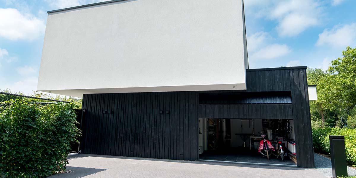 Zwarte-houten-garagedeur-verticaal-geprofileerd-in-drie-breedtes-gelijk-met-gevel-23