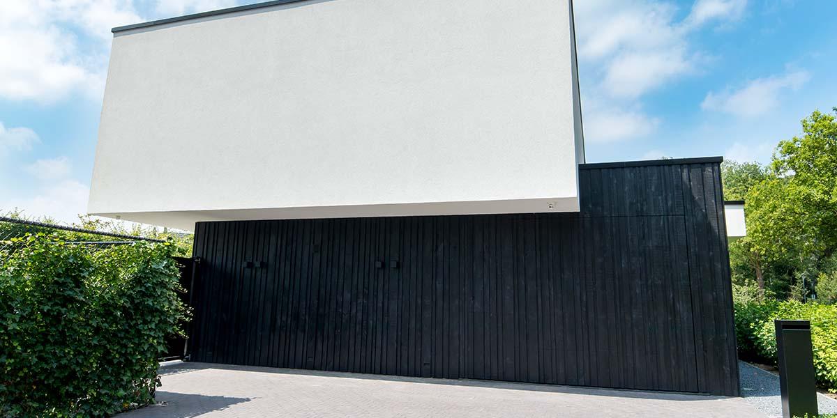 Zwarte-houten-garagedeur-verticaal-geprofileerd-in-drie-breedtes-gelijk-met-gevel-25