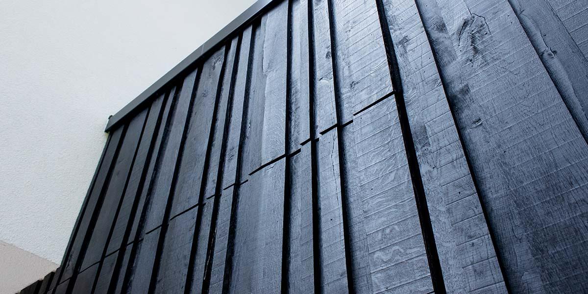 Zwarte-houten-garagedeur-verticaal-geprofileerd-in-drie-breedtes-gelijk-met-gevel-41
