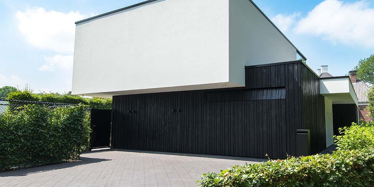 Zwarte-houten-garagedeur-verticaal-geprofileerd-in-drie-breedtes-gelijk-met-gevel-10