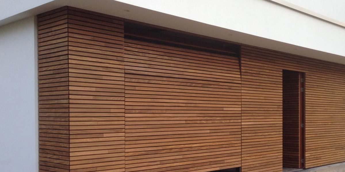https://garagedeuren.s3.amazonaws.com/20180827101631/elektrische-houten-sectionaalpoort-en-houten-loopdeur-geintegreerd-in-de-gevel-7.jpg