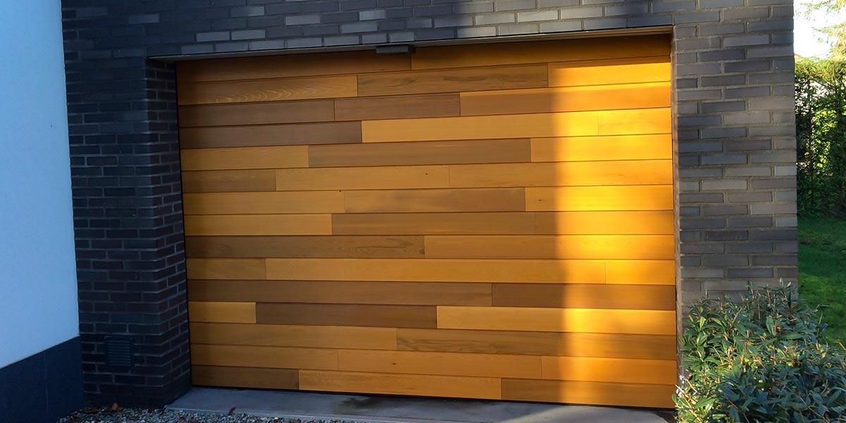 https://garagedeuren.s3.amazonaws.com/20180918122343/Red-Cedar-Houten-sectionaaldeur-elektrisch1.jpg