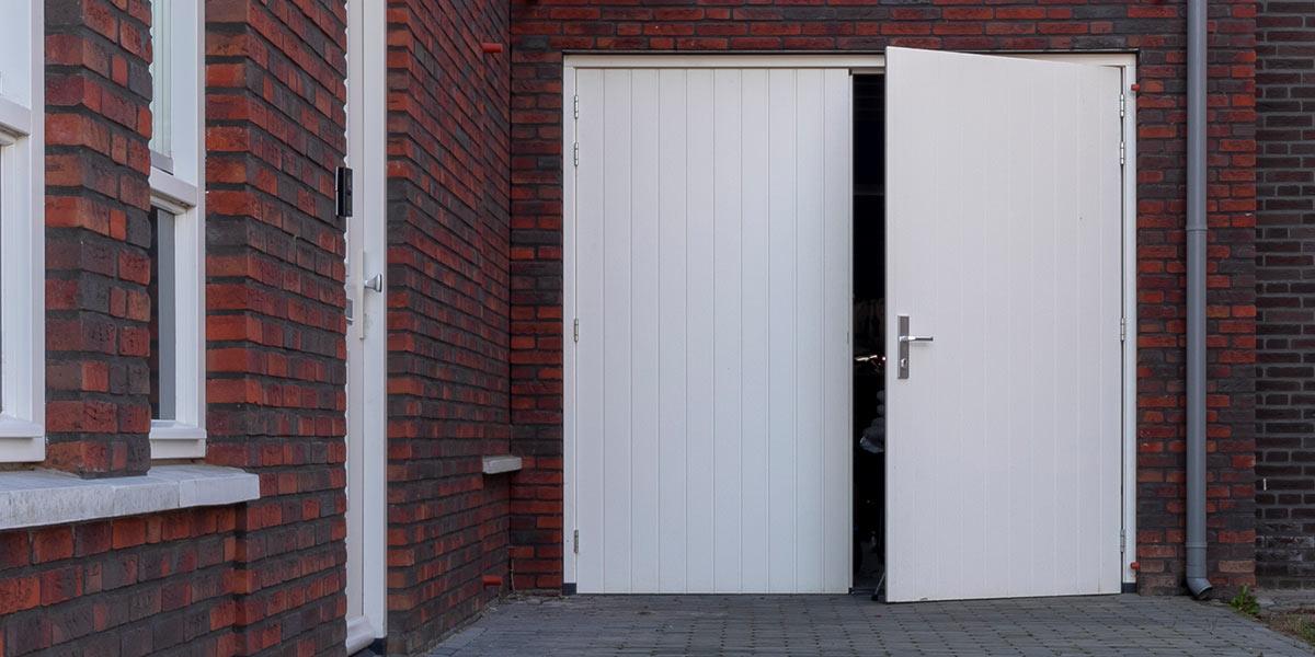 https://garagedeuren.s3.amazonaws.com/20190315144449/witte-houten-openslaande-garagedeur.jpg