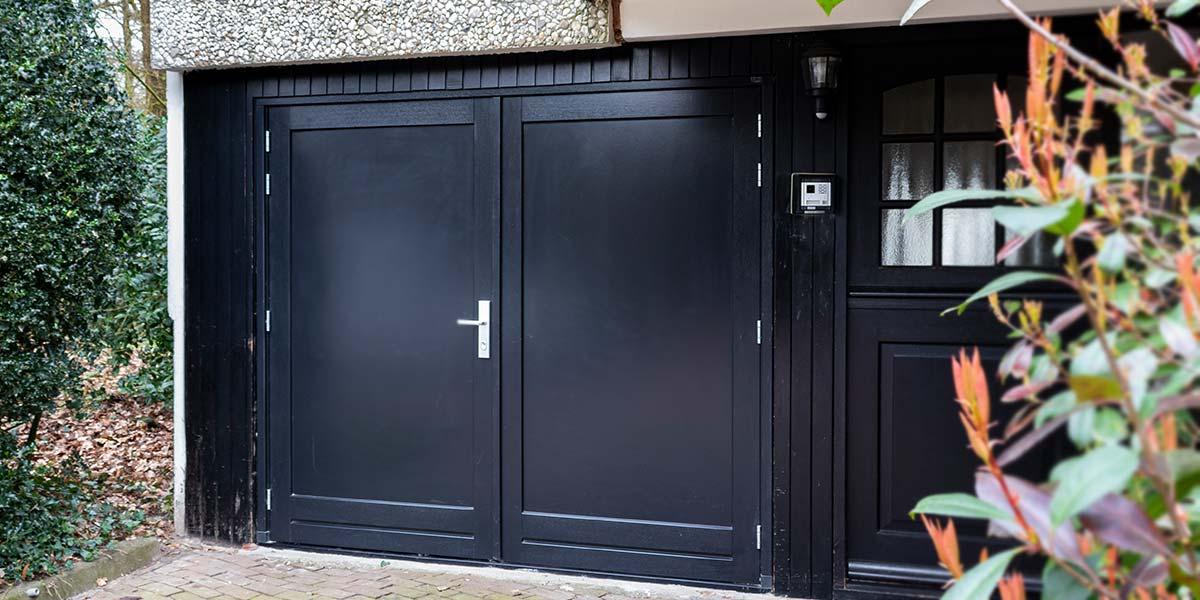https://garagedeuren.s3.amazonaws.com/20190318161440/zwarte-openslaande-garagedeur-hout.jpg