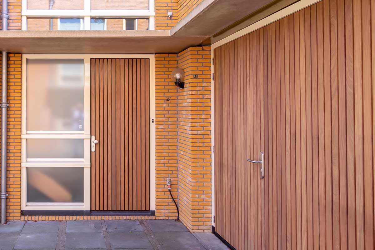 Verticale houten voordeur met houten openslaande garagedeur (2)