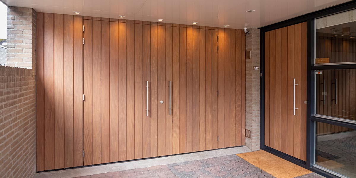 https://garagedeuren.s3.amazonaws.com/20200616080756/houten-openslaande-garagedeur-en-voordeur-.jpg