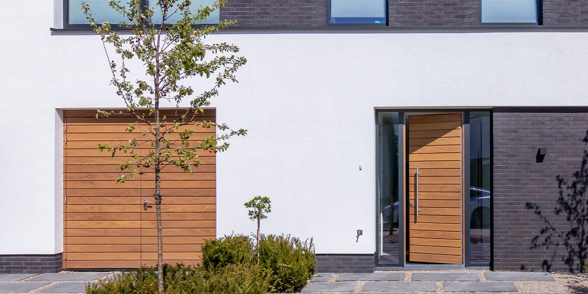 https://garagedeuren.s3.amazonaws.com/20200625160241/houten-garagedeur-en-voordeur.jpg