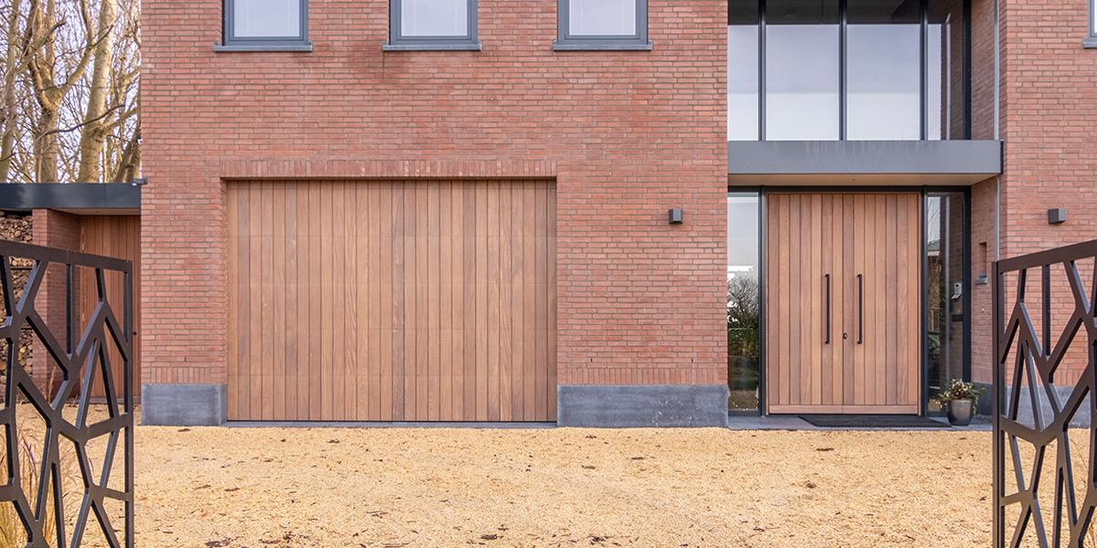 https://garagedeuren.s3.amazonaws.com/20210226105407/Verticale-houten-garagedeur-en-voordeur.jpg