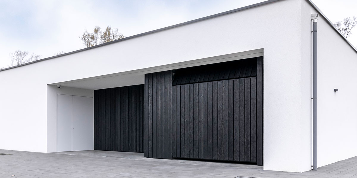 https://garagedeuren.s3.amazonaws.com/20210407162151/zwarte-gebrande-garagedeur-en-voordeur.jpg