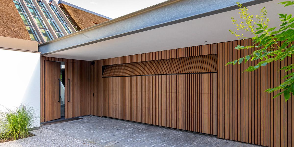https://garagedeuren.s3.amazonaws.com/20210922155049/verticale-houten-latten-garagedeur.jpg